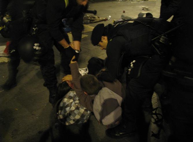 Dos manifestantes durante el desalojo del campamento en la Puerta del Sol