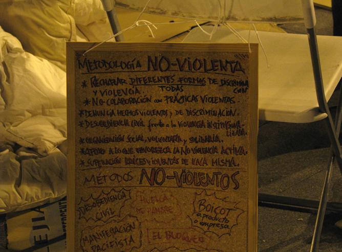 Cartel de 'Metodología No-Violenta' en la Puerta del Sol de Madrid, minutos antes de ser desalojada