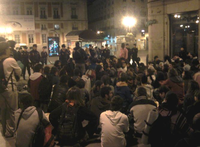 Jóvenes sentados en las proximidades de la plaza de Callao