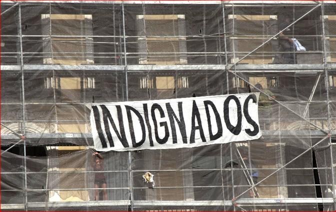Dos personas colocando una pancarta en un edificio de la Puerta del Sol