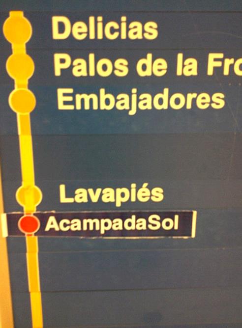 Una pegatina en el metro de Madrid indica dónde está la acampada de Sol