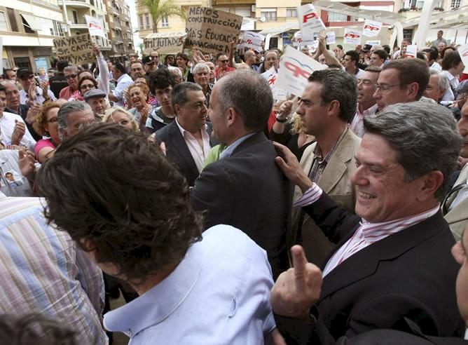 Trillo, situado en la foto detrás de Camps, hace un gesto a las personas que le increpan en Torrevieja