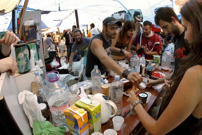 Varios jóvenes comen en el campamento que han organizado los asistentes a la protesta de la madrileña Puerta del Sol, donde miles de personas han pasado la noche acampados a pesar de la lluvia