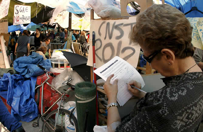 Una mujer deposita su firma en el campamento levantado en la Puerta del Sol de Madrid para apoyar la acampada que se ha organizado allí, prevista hasta el próximo domingo 22 de mayo, día de las elecciones autonómicas y locales.
