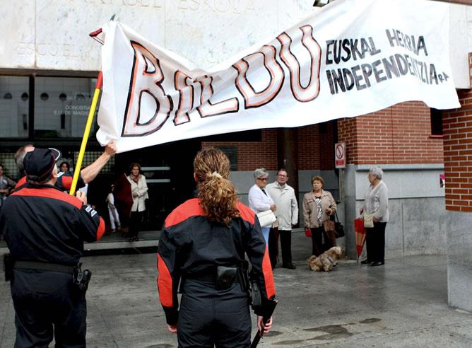 Agentes de la Ertzaintza retiran una pancarta de apoyo a Bildu de un colegio electoral en San Sebastián