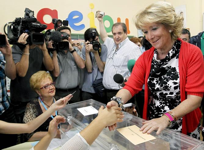 La presidenta de la Comunidad de Madrid y aspirante a la reelección, Esperanza Aguirre, saluda a una miembro de la mesa en la que depositó su voto para las elecciones autonómicas y municipales de hoy, en el colegio Pi i Margall de Madrid.