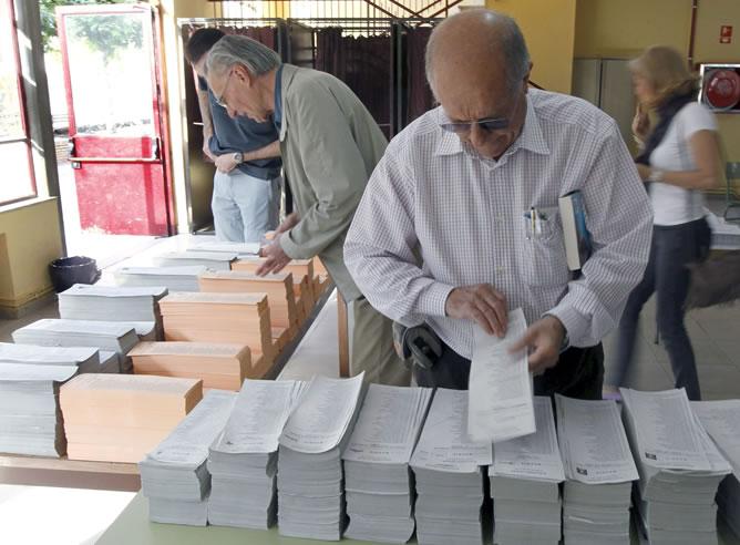 Varios madrugadores escogen sus papeletas para emitir su voto en un colegio de Aravaca, nada más abrirse las mesas electorales para los comicios autonómicos y municipales que se celebran hoy