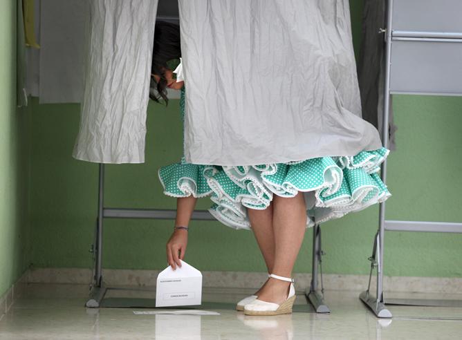 Una joven vestida de flamenca recoge del suelo su voto en una cabina del colegio electoral de la Fuensanta de Córdoba, donde las elecciones municipales coinciden con la celebración de la Feria de esta ciudad.