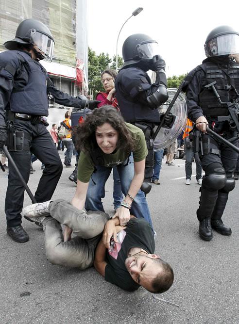 Una de las concentradas en la plaza de Cataluña ayuda a un compañero ante la presencia de los Mossos d'Esquadra que la han desalojado esta mañana.