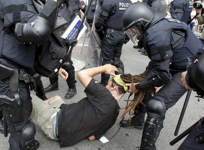 """Los Mossos d'Esquadra han cargado hoy contra los """"indignados"""" de plaza de Cataluña de Barcelona, después de que éstos intentaran evitar la salida de la plaza de los camiones de limpieza que retiraban sus pertenencias. Una cincuentena de personas han resultado heridas leves y al menos se ha producido una detención."""