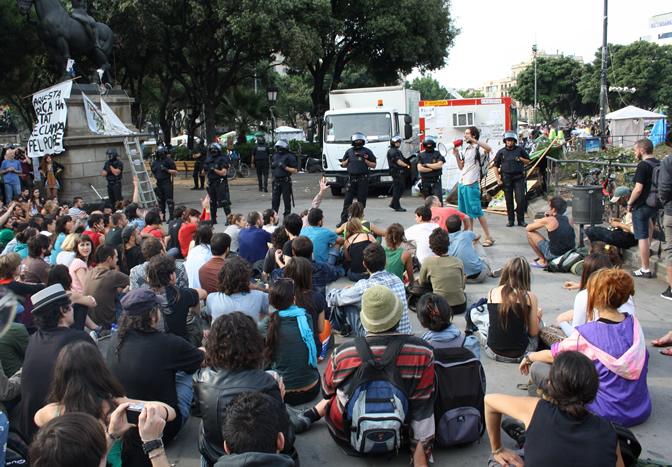 Jóvenes del movimiento 15-M esperan sentados en el centro de la plaza Cataluña el desalojo de los Mossos, que buscan que los servicios de limpieza aseen la plaza