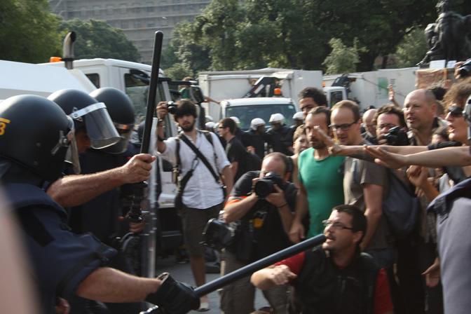 Los agentes, que portan porras y escudos, sacan por la fuerza a las personas que permanecían en la plaza barcelonesa