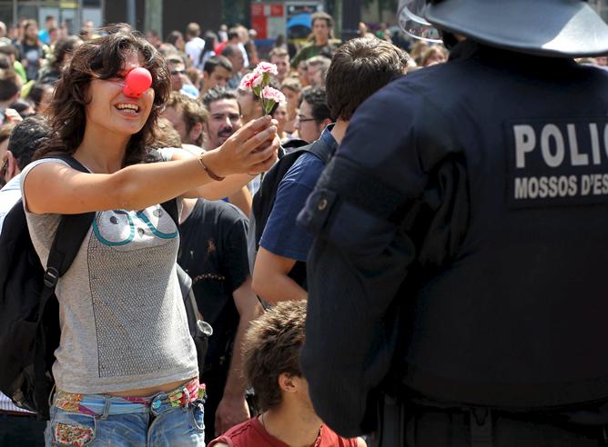 Una joven sostiene un clavel en su mano ante la presencia de un agente de los Mossos d'Esquadra, que han participado en el dispositivo para desalojar la plaza Cataluña.