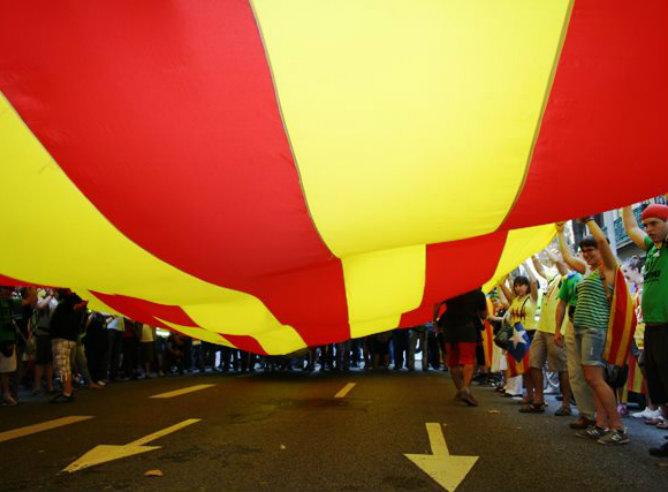 Varias decenas de catalanes ondean una bandera gigante de Cataluña