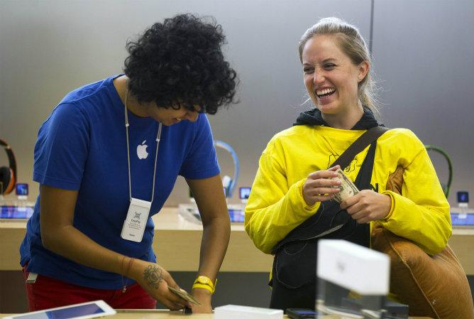 Un cliente junto a un empleado de la tienda de Apple después de comprar un  iPhone 5 en la 5ª Avenida en Nueva York