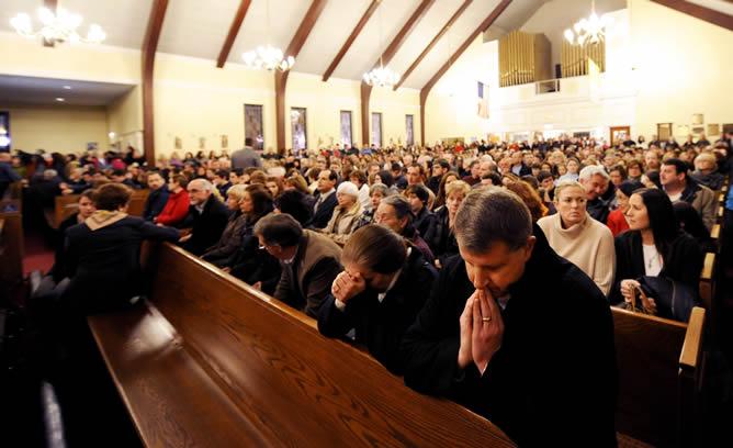 Decenas de ciudadanos llenan una iglesia en una vigilia por las víctimas del tiroteo en la escuela infantil estadounidense Sandy Hook