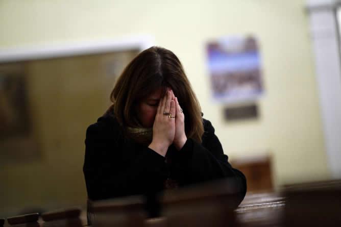 Una mujer reza en recuerdo de las víctimas tras la tragedia vivida en un colegio infantil de Newton.