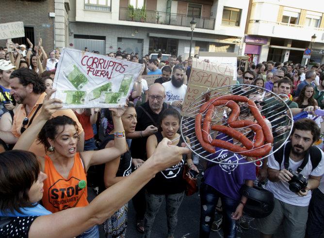 Una manifestante sostiene chorizos durante una manifestación en la sede del Partido Popular en Valencia