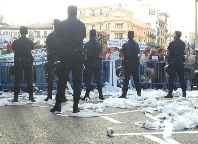 Los manifestantes lanzan rollos de papel higiénico a la policía después de que hayan cortado la calle Génova desde Colón