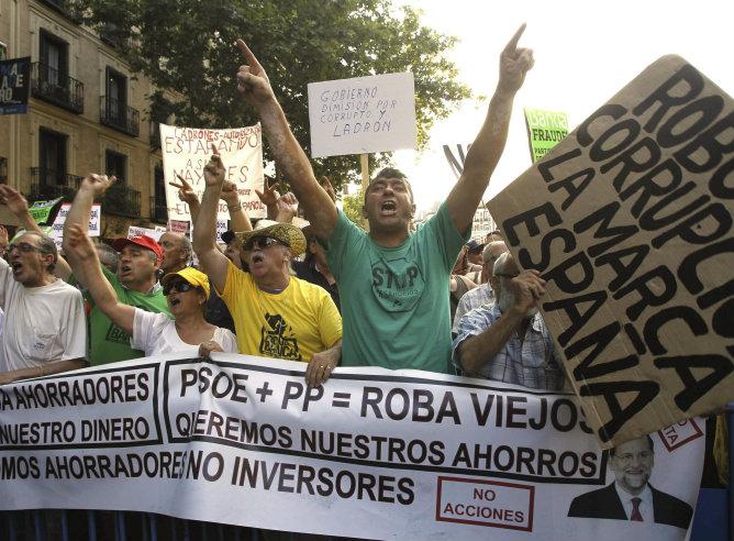 Varias personas sostienen pancartas ante la sede del PP en Madrid durante la concentración convocada por varios colectivos