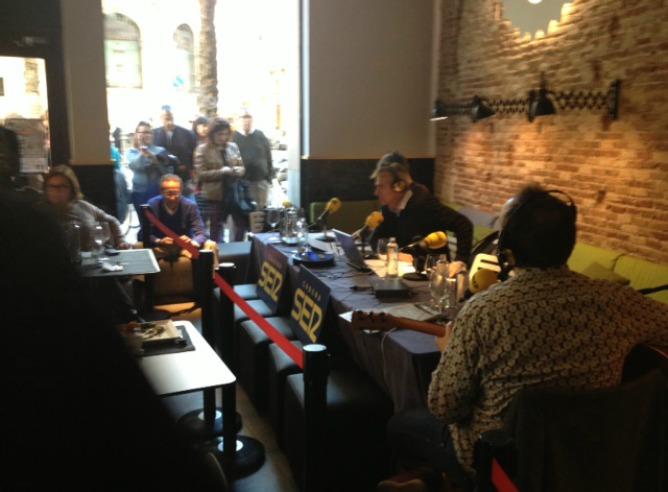 Varias personas miran el 'estudio' improvisado de 'La Ventana' en el café el Lotelito