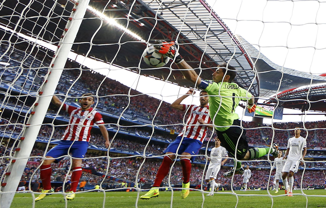Casillas despeja la pelota dentro de su propia portería ante la mirada de Adrián y Raúl García.