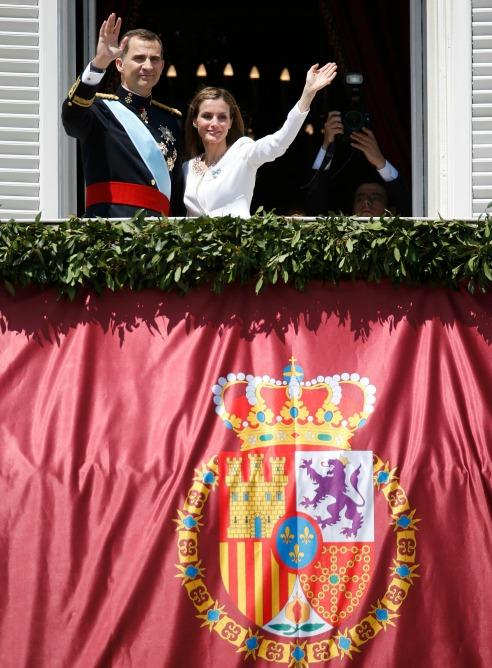 Los reyes de España saludan desde el balcón del Palacio Real.