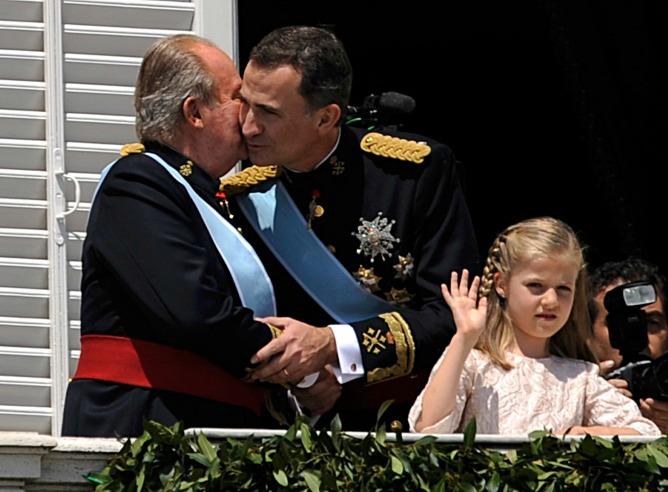 Felipe VI abraza a su padre, el rey Juan Carlos, en el balcón del Palacio Real.