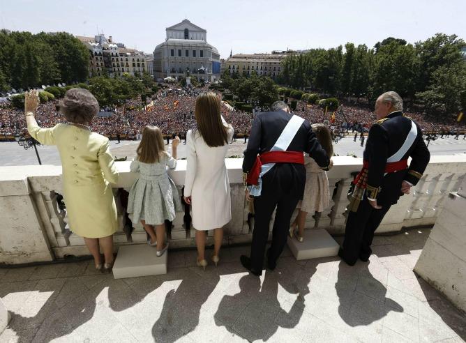 Los reyes, Felipe VI y Letizia, junto a sus hijas, Leonor, princesa de Asturias, y la infanta Sofía, y don Juan Carlos y doña Sofía, saludan desde el balcón central del Palacio de Oriente.