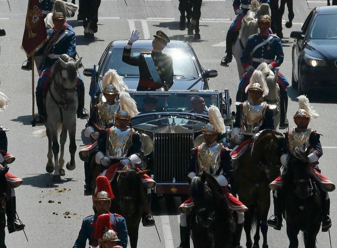 El rey Felipe VI y la reina Letizia, en su trayecto hacia el Palacio Real en un Rolls Royce descapotable, perteneciente a Patrimonio Nacional.