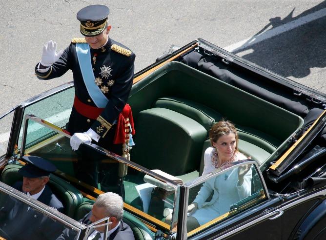 Felipe VI y la reina Letizia saludan desde el coche, en el paseo por Madrid tras la proclamación.