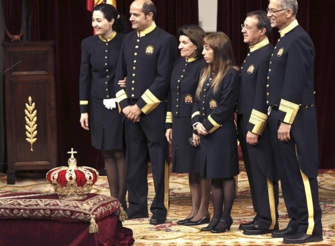 Los ujieres del Congreso de los Diputados se fotografian junto a la corona en el interior del hemiciclo.