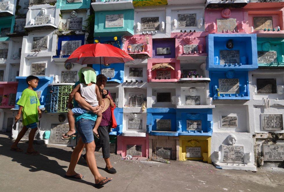Una familia pasa delante de las tumbas decoradas por el Día de todos los Santos en Marikina, Filipinas, el páis católico más importante de Asia