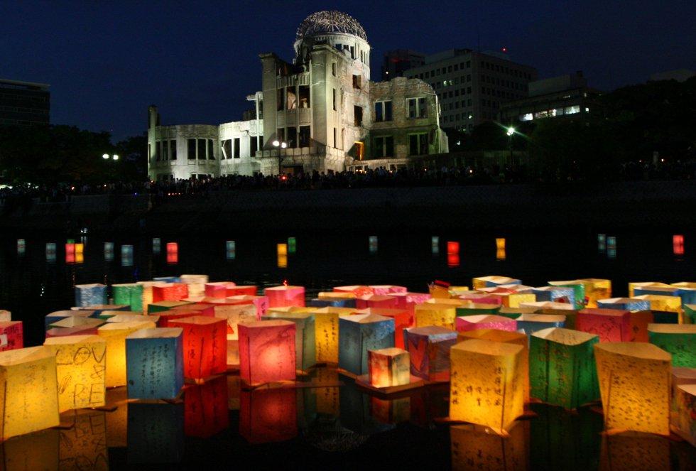 Linternas de papel flotan en el río Motoyasu delante de la Paz de Hiroshima ,comúnmente llamado la Cúpula de la Bomba Atómica , en el Parque Memorial de la Paz de Hiroshima el 6 de agosto de 2012 en Hiroshima .