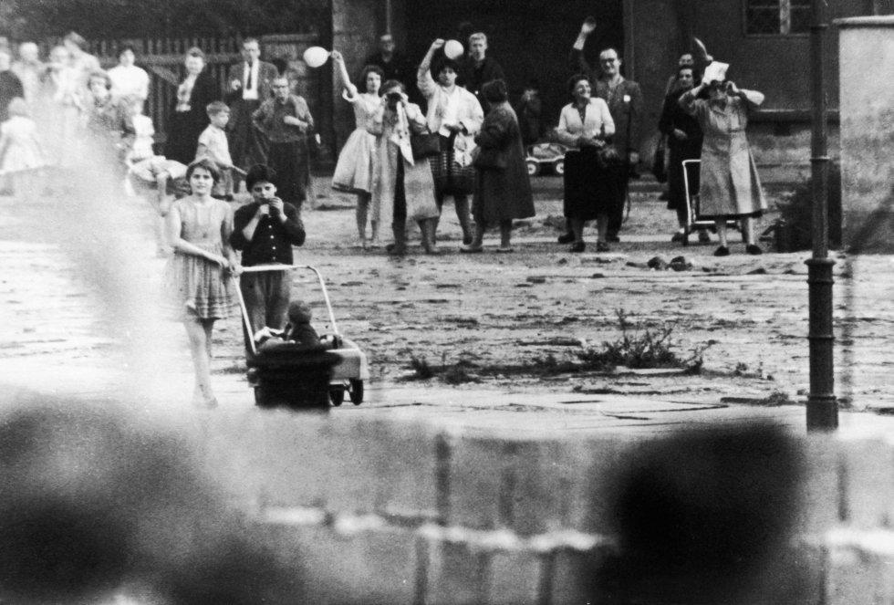 Familias y amigos que una vez fueron vecinos, se saludan de un lado a otro del muro que les divide. Imagen tomada en 1961.
