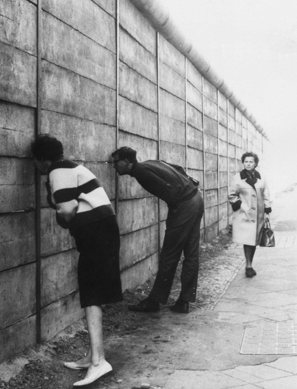 Berlineses occidentales mirando a través del Muro de Berlín en el sector oriente cerca de Check Point Charlie. La pared recién erigida no tiene alambre de púas. Los tubos hacen que sea difícil lograr un apoyo a alguien que trate pasar por encima. Imagen de archivo del 3 de octubre de 1966.