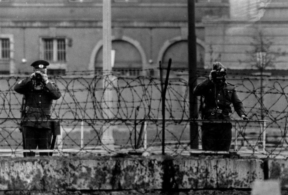 Guardias de Alemania del Este miran por encima del muro de Berlín durante la visita de la reina Isabel y del príncipe Felipe a la ciudad, el 29 de mayo 1965.