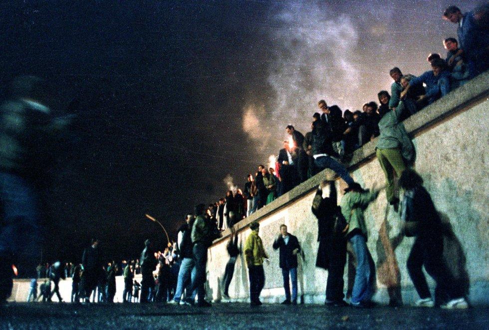 Los ciudadanos de Alemania del Este trepan al muro de Berlín tras la apertura de la frontera de Alemania Oriental. Imagen de archivo tomada el 9 de noviembre de 1989.