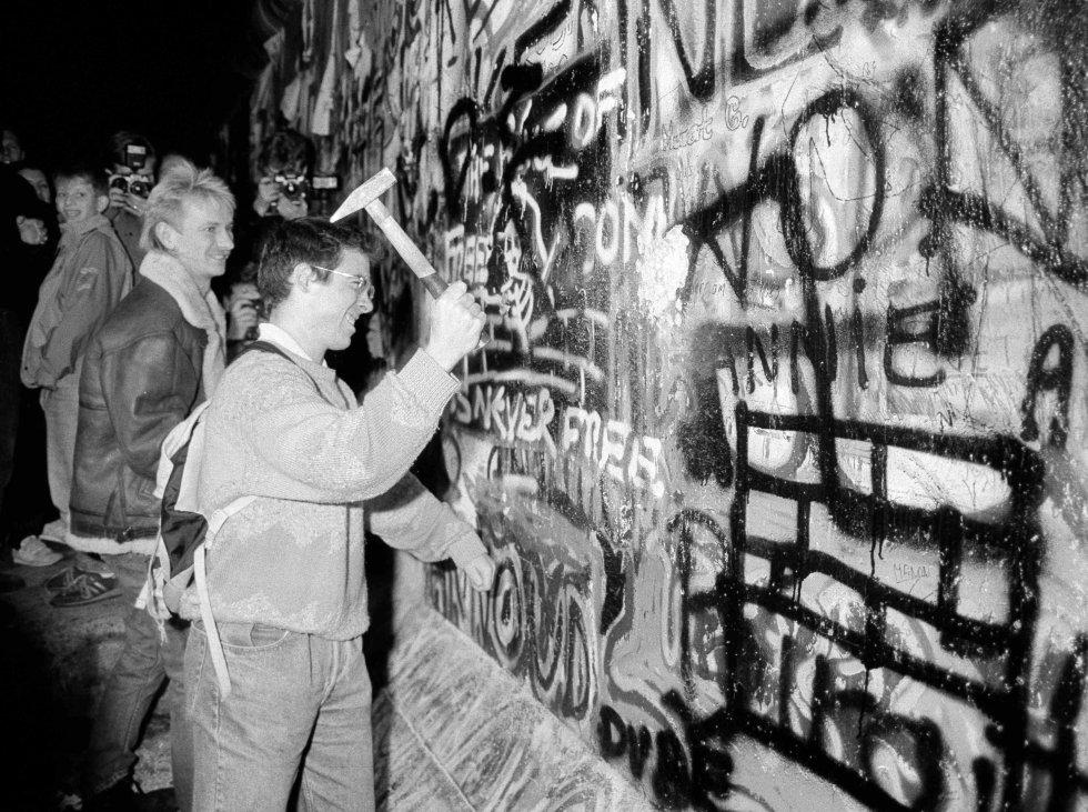 Un hombre golpea con un martillo una sección del muro de Berlín, cerca de la Puerta de Brandenburgo, tras la apertura de la frontera de Alemania del Este. Imagen de archivo tomada el 9 de noviembre de 1989.