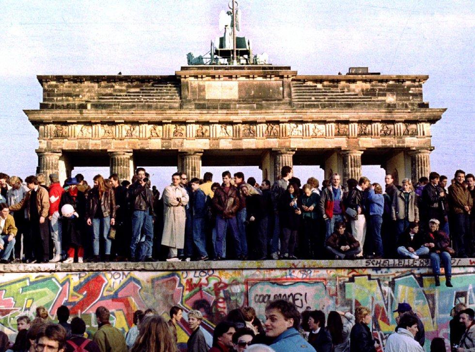 Ciudadanos vigilan en lo alto del muro de Berlín frente a la Puerta de Brandenburgo. Imagen de archivo tomada el 10 de noviembre de 1989.