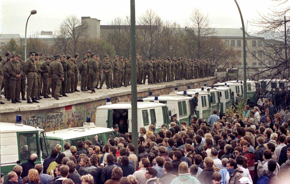 Cientos de guardias fronterizos del Este Berlín situados sobre el muro en la Puerta de Brandenburgo se enfrentan a los ciudadanos de Berlín occidental. Imagen de archivo tomada el 11 de noviembre de 1989.