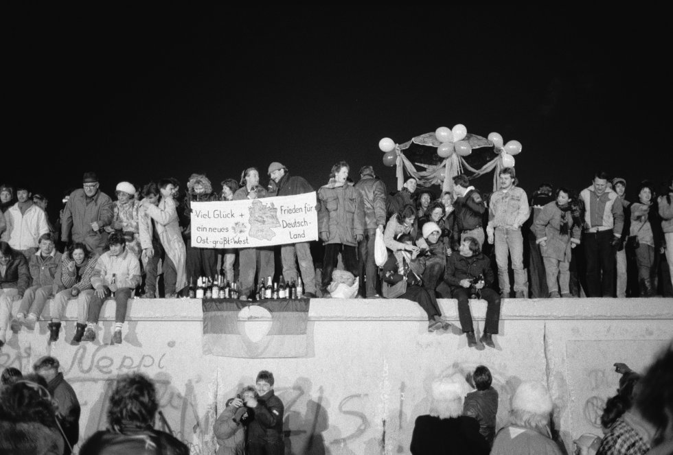 """Los berlineses se reunieron en el Muro de Berlín para celebrar el Año Nuevo y el fin efectivo de la partición de la ciudad el 31 de diciembre de 1989. En la pancarta se lee """"Buena suerte y paz para una nueva Alemania - el este saluda al oeste""""."""