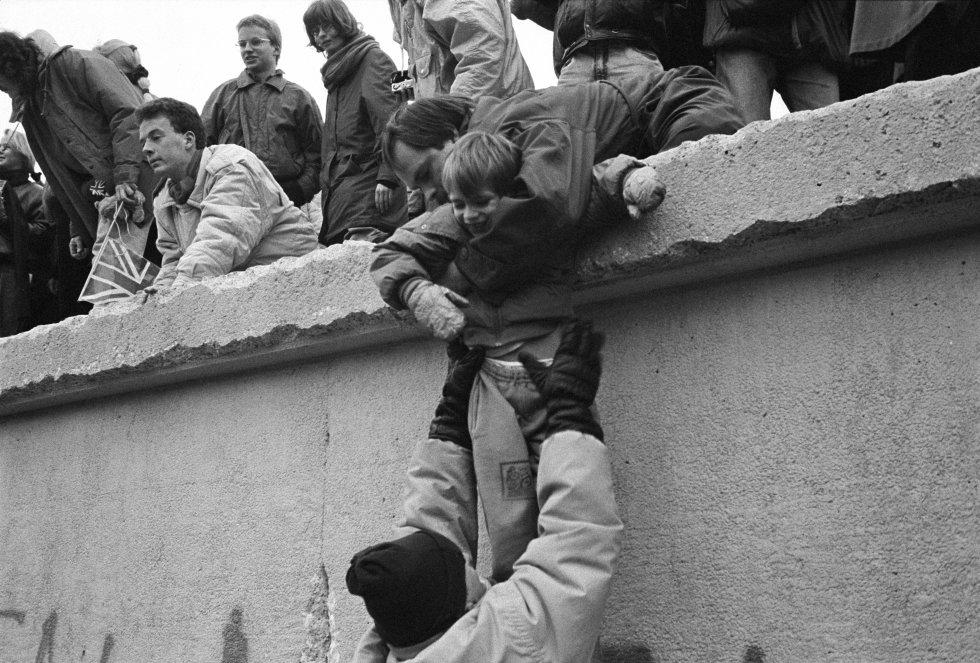 Los berlineses del Este se suben al muro de Berlín para celebrar el final efectivo de la partición de la ciudad, el 31 de diciembre de 1989.