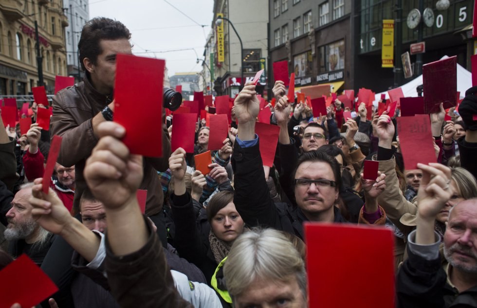 Manifestantes muestran tarjetas rojas en una protesta contra el presidente checo, Milos Zeman, junto a un memorial dedicado a los estudiantes que fueron atacados por la policía en 1989