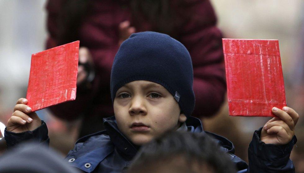 Un niño muestra un par de tarjetas rojas en una manifestación contra el presidente checo, Milos Zeman