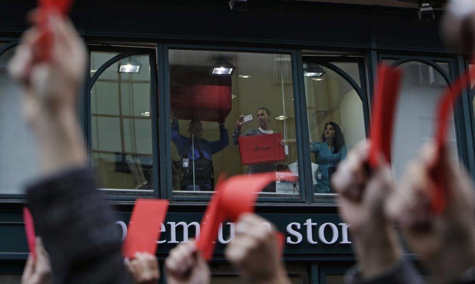 Empleados de una tienda de Praga y manifestantes muestran tarjetas rojas, el símbolo de las protestas contra el actual presitente checo, Milos Zeman