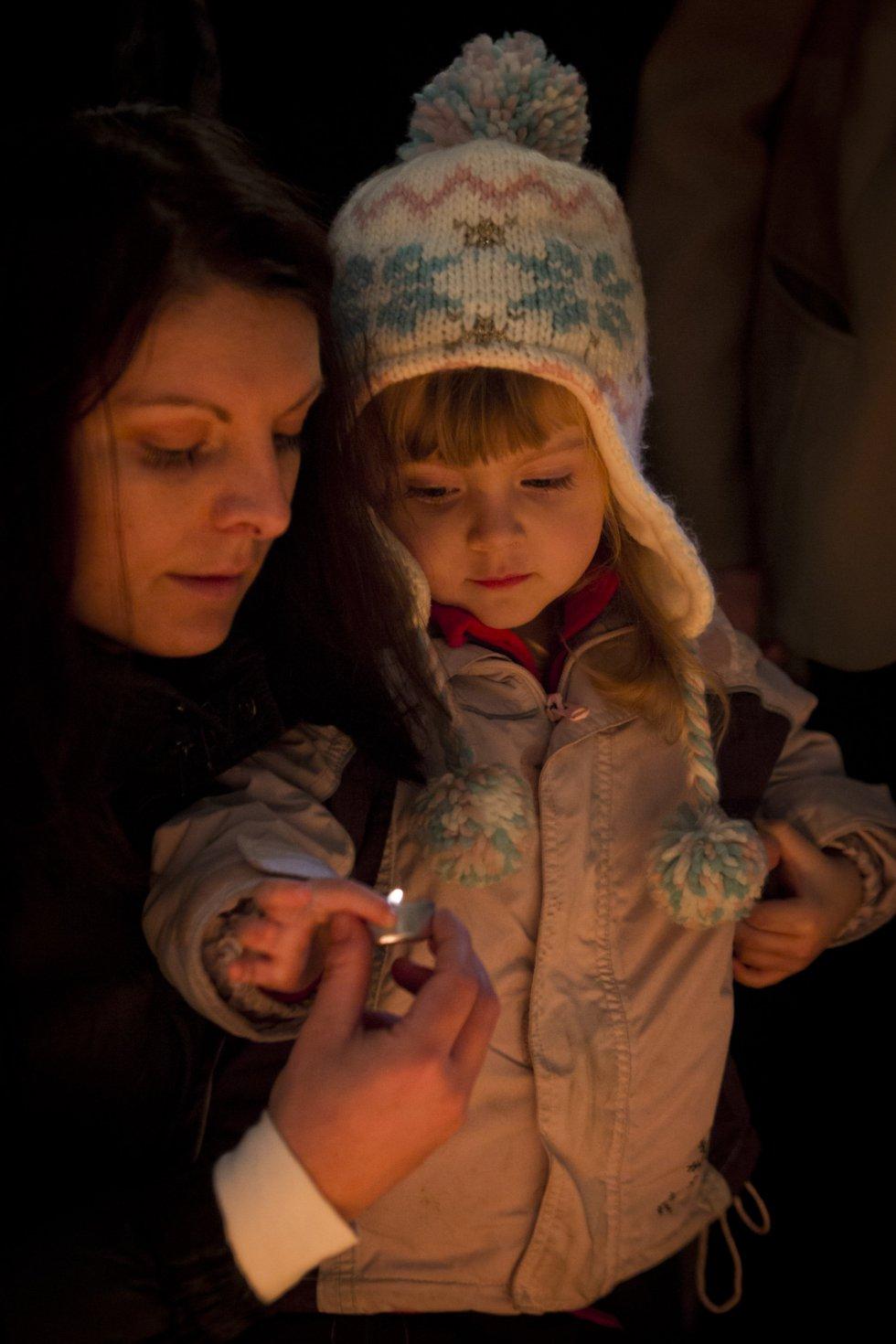 Una mujer y su hija encienden una vela en recuerdo de los estudiantes que fueron atacados por la policía en 1989