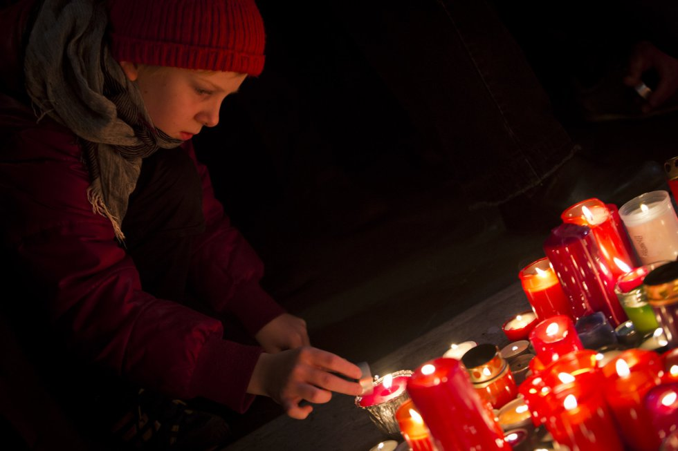 Un niño enciende una vela en recuerdo de los estudiantes que fueron atacados por la policía en 1989