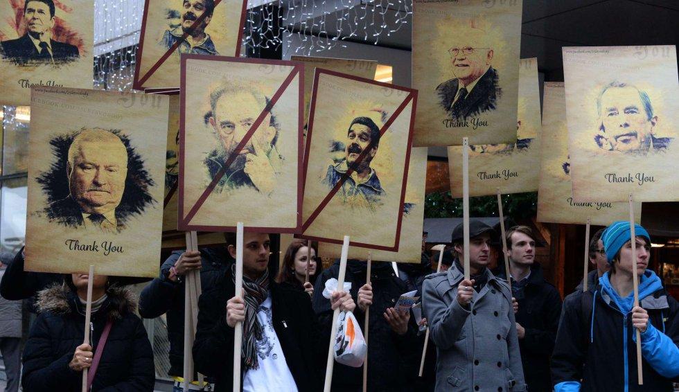 Manifestantes muestran retratos de políticos durante una manifestación contra el acercamiento del actual presidente checo a Rusia, en el 25 aniversario de la 'Revolución delos Claveles'