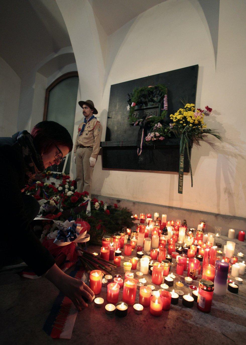 Una mujer enciende una vela en recuerdo de los estudiantes que fueron atacados por la policía en 1989